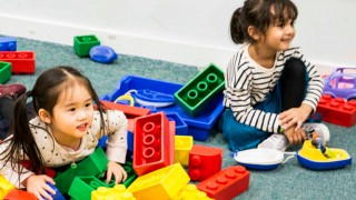 two small girls playing in a pile of giant lego